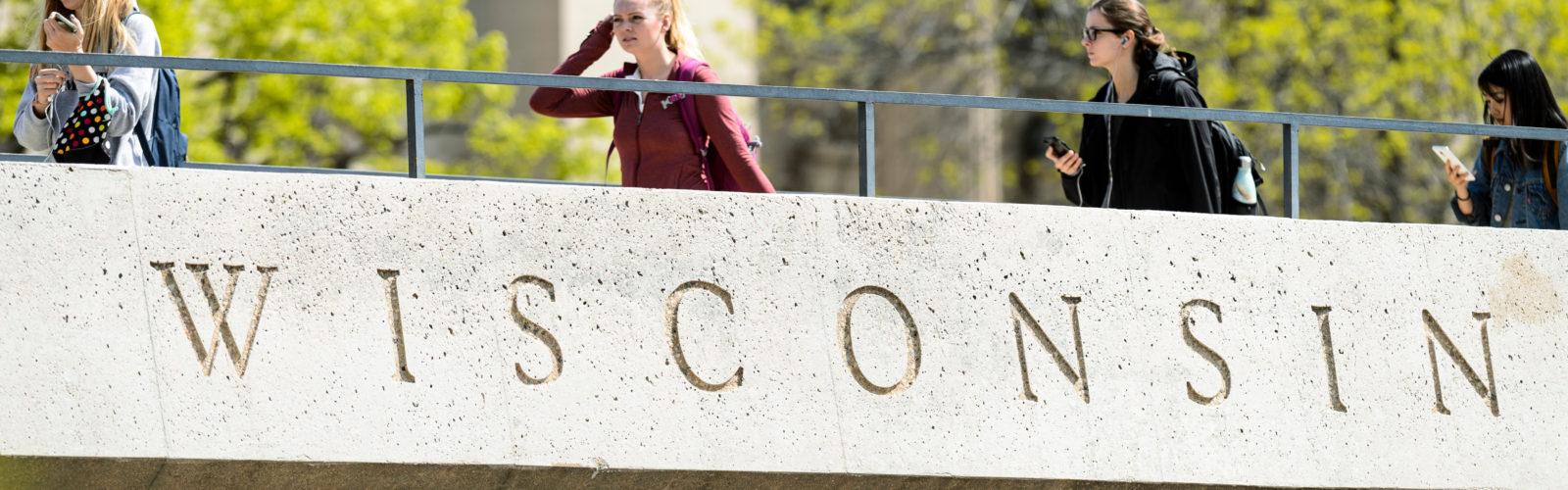 Students walk across the North Park Street pedestrian overpass bridge